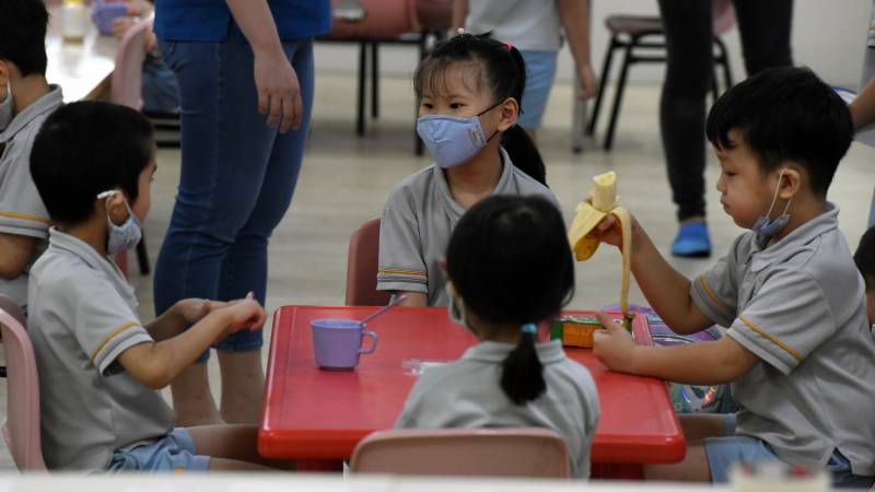 Back to school in masks as Singapore eases virus curbs