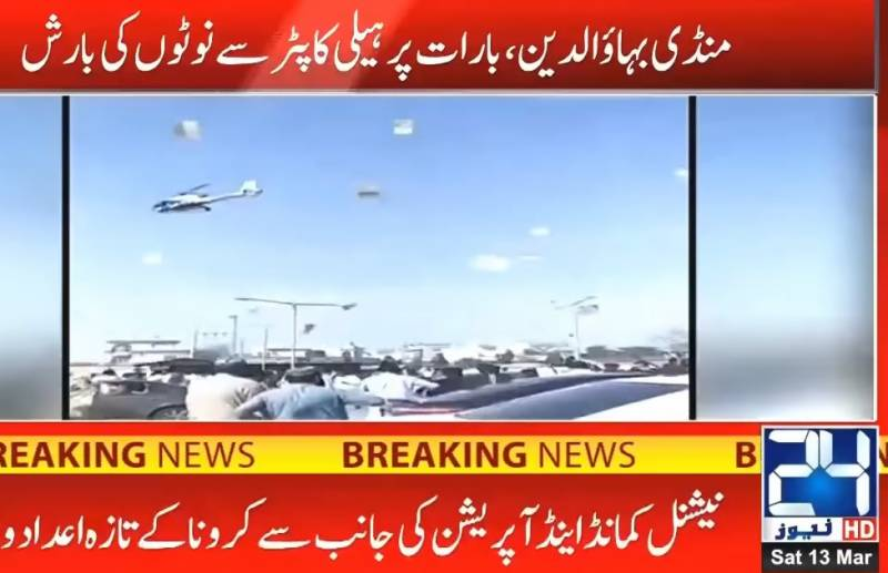 Helicopter showers currency notes on wedding party
